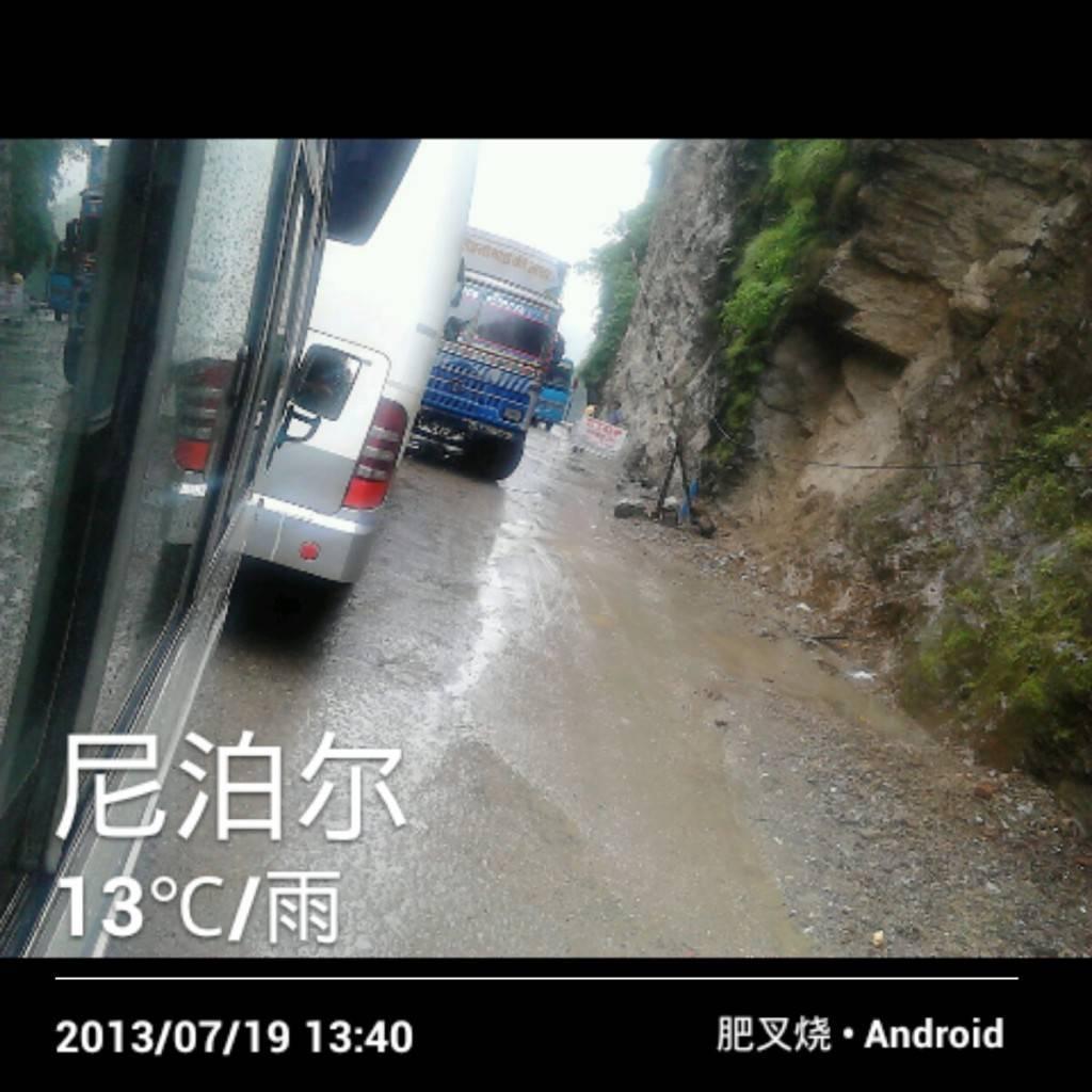 悬崖陡壁,下着雨,路面各种泥水流。